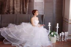 Sch?ne junge Braut in einem wei?en Kleid mit sch?nen Dekorationen stockfotografie