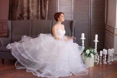 Sch?ne junge Braut in einem wei?en Kleid mit sch?nen Dekorationen lizenzfreies stockfoto