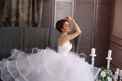 Sch?ne junge Braut in einem wei?en Kleid mit sch?nen Dekorationen lizenzfreie stockfotos
