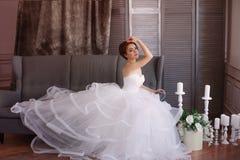 Sch?ne junge Braut in einem wei?en Kleid mit sch?nen Dekorationen stockfotos