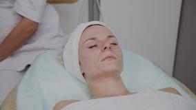 Sch?ne junge Frau in Bademantell?genund Wartegesichtspflegeverfahren am Luxusbadekurortsalon stock video footage