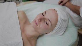 Sch?ne junge Frau in Bademantell?genund Wartegesichtspflegeverfahren am Luxusbadekurortsalon stock footage