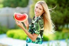 Sch?ne junge Frau, die eine Scheibe der Wassermelone zeigt Sie ist kaukasisch Sommer- und Lebensstilkonzepte stockfoto