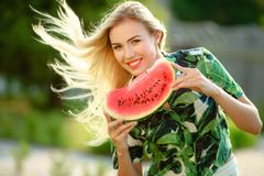 Sch?ne junge Frau, die eine Scheibe der Wassermelone zeigt Sie ist kaukasisch Sommer- und Lebensstilkonzepte lizenzfreie stockbilder
