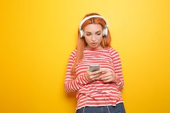 Sch?ne junge Frau, die Musik auf Farbhintergrund h?rt lizenzfreie stockfotos