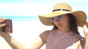 Sch?ne junge Frau, die selfie auf Strand nimmt stock footage