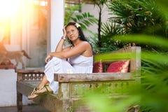 Sch?ne junge Frau im wei?en Kleid, das auf Weinlesesofa im Garten stillsteht Reise- und Sommerkonzept stockfotos