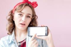 Sch?ne junge Frau mit Stift-obenmake-up und -frisur ?ber rosa Hintergrund mit Handy mit Kopienraum stockbilder