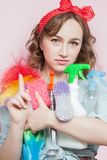 Sch?ne junge Frau mit Stift-obenmake-up und -frisur mit Reinigungswerkzeugen auf rosa Hintergrund stockfotografie