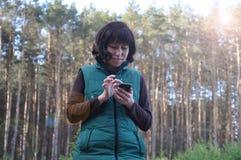 Sch?ne junge Frau Schauen im Telefon aus dem Wald heraus stockbild