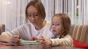 Sch?ne junge Frau zeichnet mit ihrer netten kleinen Tochter stock footage
