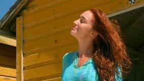 Sch?ne junge kaukasische Frauenstellung auf Strandh?tte im Sonnenschein stock video