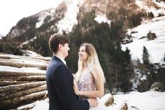 Sch?ne junge Paare in den Winterbergen Winterweg von Liebhabern Mann, der Frau umarmt stockfotos