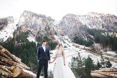 Sch?ne junge Paare in den Winterbergen Winterweg von Liebhabern Mann, der Frau umarmt stockbild