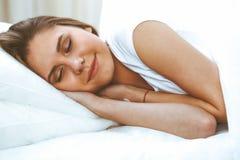 Sch?ne junge und gl?ckliche schlafende Frau beim im Bett bequem liegen und himmlisch l?cheln stockbild