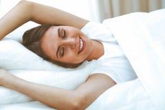 Sch?ne junge und gl?ckliche schlafende Frau beim im Bett bequem liegen und himmlisch l?cheln lizenzfreie stockfotos