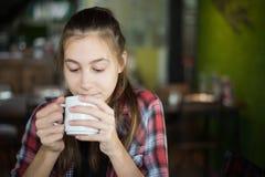 Schöne kaukasische Frau, die einen Tasse Kaffee in ihrer Hand auf unscharfem Hintergrund hält lizenzfreie stockfotografie