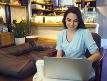 Sch?ne Mischrassefrau, die in einer Kaffeestube unter Verwendung ihres Laptops sitzt stockfotos