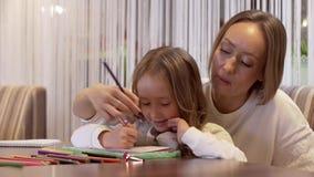 Sch?ne Mutter der jungen Frau zeichnet mit ihrer netten kleinen Tochter stock video footage