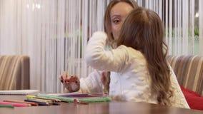 Sch?ne Mutter der jungen Frau zeichnet mit ihrer netten kleinen Tochter stock footage