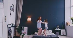 Sch?ne Mutter und Tochter haben Spa? beim auf Bett zu Hause springen stock video footage