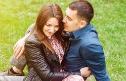 Sch?ne romantische Paare, die am Fr?hlingsgr?npark umfassen lizenzfreie stockfotografie