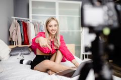 Sch?ner junges M?dchen Blogger gekleidet in der hellen modernen Kleidung, die auf dem Bett mit einem Laptop sitzt und Video herst lizenzfreies stockbild