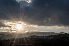 Sch?ner Sonnenuntergang Sun-Einstellung hinter Bergen Drastische Wolken Tag zur Nacht Verdunkelungshimmel am Abend Strahlen der L stockbild