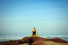 Sch?nes ?bendes Yoga der jungen Frau und ?bungen am Sommerozeanstrand ausdehnen stockfoto