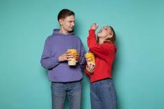 Sch?nes blondes M?dchen im roten Hoodie Popcorn von ihrem Freund, jungen Mann stehlend, der emp?rt sie betrachtet stockfotos