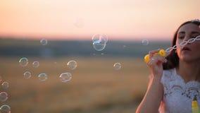 Sch?nes Braut- und Br?utigamlachen und Schlagseifenblasen im Park bei Sonnenuntergang stock video
