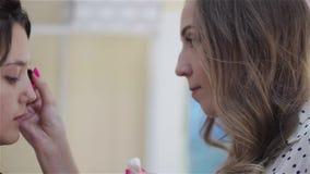 Sch?nes brunette M?dchen verwendet die Services eines Berufsmaskenbildner Kosmetiksalons Make-upk?nstler und ihr Kunde stock video
