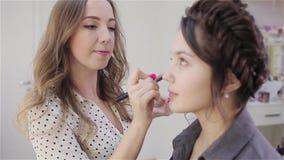 Sch?nes brunette M?dchen verwendet die Services eines Berufsmaskenbildner Kosmetiksalons Make-upk?nstler und ihr Kunde stock video footage