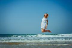 Sch?nes Joyfull-M?dchen, das auf den Strand springt Ferien und Entspannung stockbild