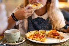 Sch?nes junges M?dchen, das eine Scheibe der Pizza isst stockfoto