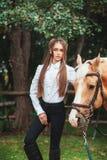 Sch?nes junges M?dchen des Portr?ts im wei?en Hemd und in den schwarzen Hosen mit folgendem Pferd des langen Haares der Sch?nheit lizenzfreies stockbild