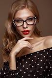Sch?nes M?dchen in der stilvollen Kleidung mit Gl?sern f?r Vision und rote sexy Lippen stockbild