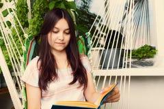 Sch?nes M?dchen mit dem langen dunklen Haar liest ein Buch, das in einer H?ngematte auf dem Balkon sitzt lizenzfreie stockfotos