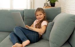 Sch?nes nettes bezauberndes kleines M?dchen, welches das Internet auf dem Laptop zu Hause l?chelt spielt und surft lizenzfreie stockfotos