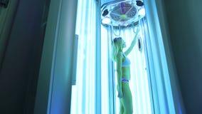 Sch?nes und athletisches M?dchen in einem wei?en Badeanzug ein Sonnenbad nehmend im Solarium stock video footage