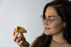Sch?nes und gl?ckliches Frauenportr?t, das hamantash Purim-Aprikosenpl?tzchen isst stockfotografie