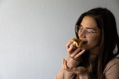 Sch?nes und gl?ckliches Frauenportr?t, das hamantash Purim-Aprikosenpl?tzchen isst lizenzfreie stockfotografie
