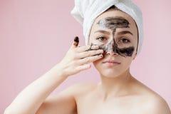 Sch?nheits-kosmetische Schale Nahaufnahme-sch?ne junge Frau mit Schwarzem ziehen weg Maske auf Haut ab Nahaufnahme der attraktive stockbild