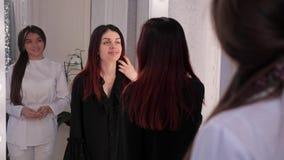 Sch?nheits-Studio Der Kosmetiker meldet den Rahmen, dann den Kunden an Kunde betrachtet im Spiegel beautician stock video footage