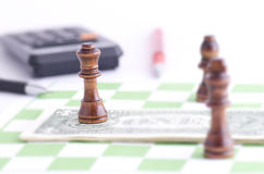 Schaak en dollars op een schaakraad Stock Fotografie