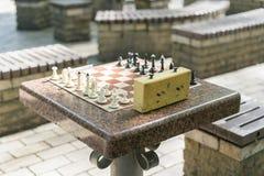 Schaakraad met stukken en klok op houten bureau met betrekking tot de schaaktoernooien Schaaktoernooien met schaak stock foto