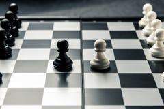 Schaakraad met zwart-wit schaak die elkaar onder ogen zien De witte en zwarte panden gaan op de aanval stock fotografie