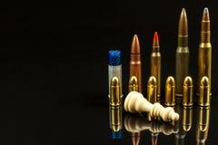 Schaakstukken en munitie op een zwarte achtergrond Spelschaak checkmate Het concept nederlaag en overwinning Gevaarlijk Spel stock foto