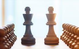 Schaakstukken lichte, donkere bruine kleur Sluit omhoog mening van koningen en panden met detail De achtergrond van het onduideli Stock Foto