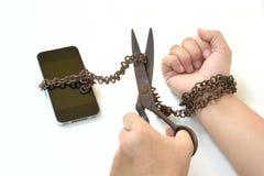Schaar die roestige ijzerketting proberen te snijden die hand en slimme telefoon samenbindt Stock Foto's